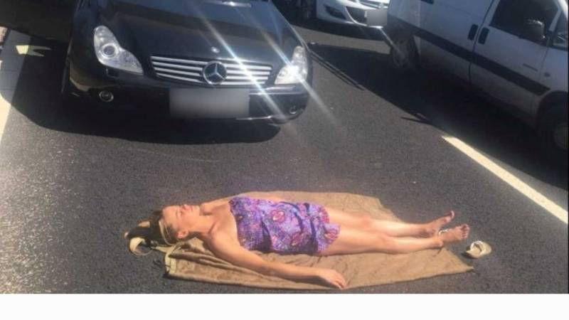 """""""Я на солнышке лежу"""": женщина улеглась позагорать между машинами, стоявшими в пробке"""