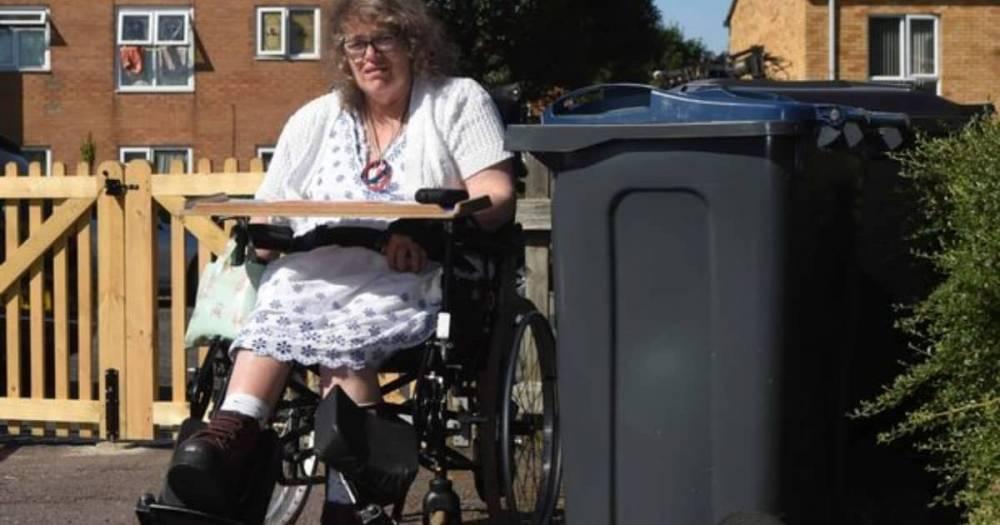 Женщина-инвалид выпала из инвалидной коляски, пытаясь проехать мимо мусорных баков, которые стояли посреди улицы